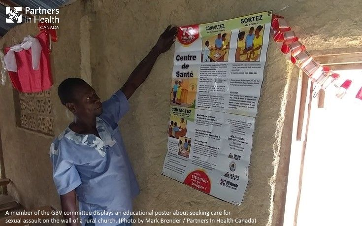 A member of the GBV committee displays an educational poster about seeking care for sexual assault on the wall of a rural church. (Photo by Mark Brender / Partners In Health Canada)