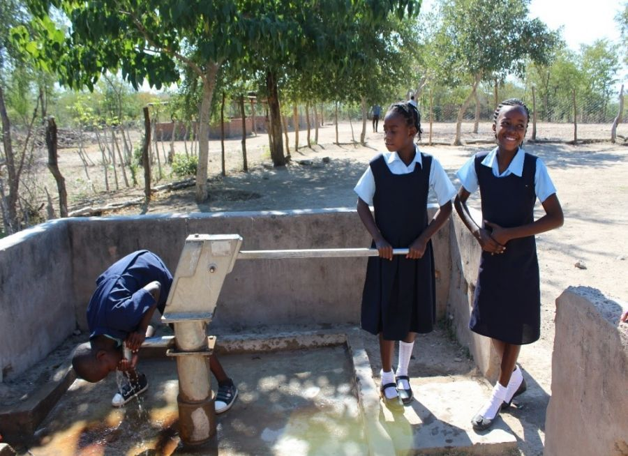 Students from the Mweela School take turns drinking water from the borehole Operation Eyesight drilled near the school.