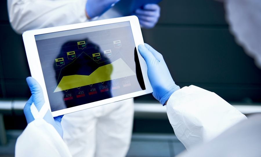 A person with surgical gloves on holding a tablet with data displayed