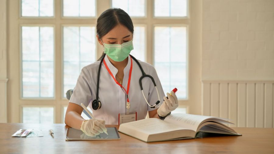 nurse charting while wearing PPE