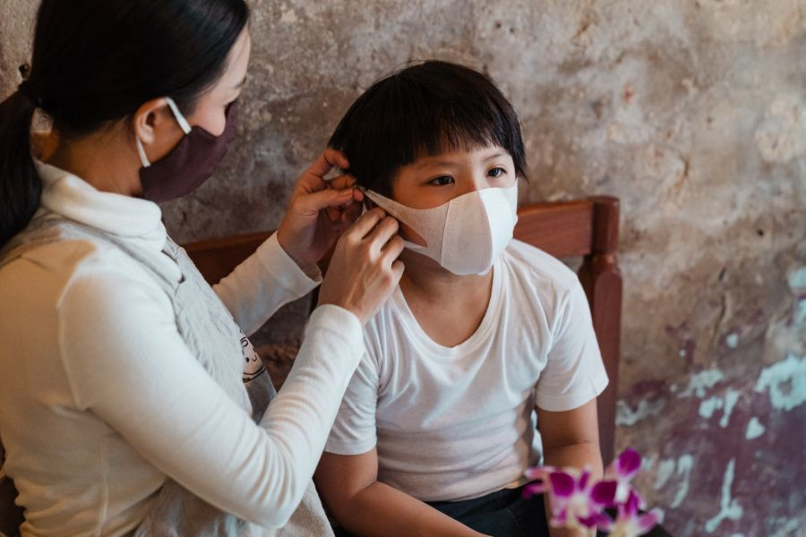mother putting a mask on her son