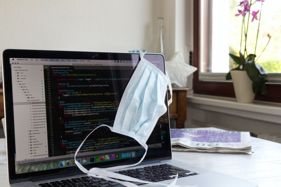 laptop computer with a surgical mask hanging off of the corner of the screen