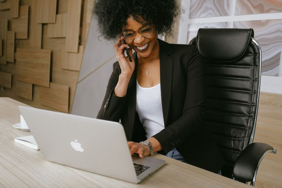 Professionally dressed Black woman speaking on the phone while also using her laptop