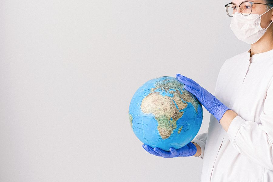 Person with a mask and latex gloves holding a globe