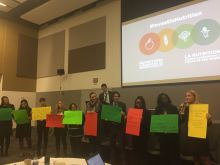 Conference attendees hold up poster boards with their own commitments.