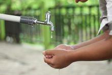 Child's hands under a running tap