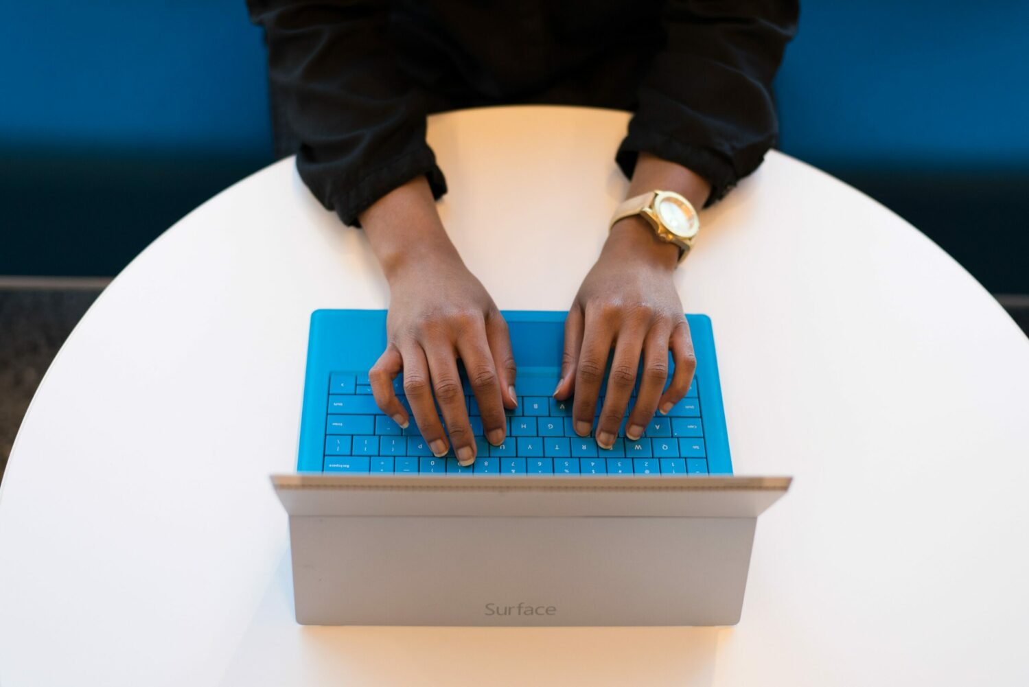 Person's hands hovering over an open laptop