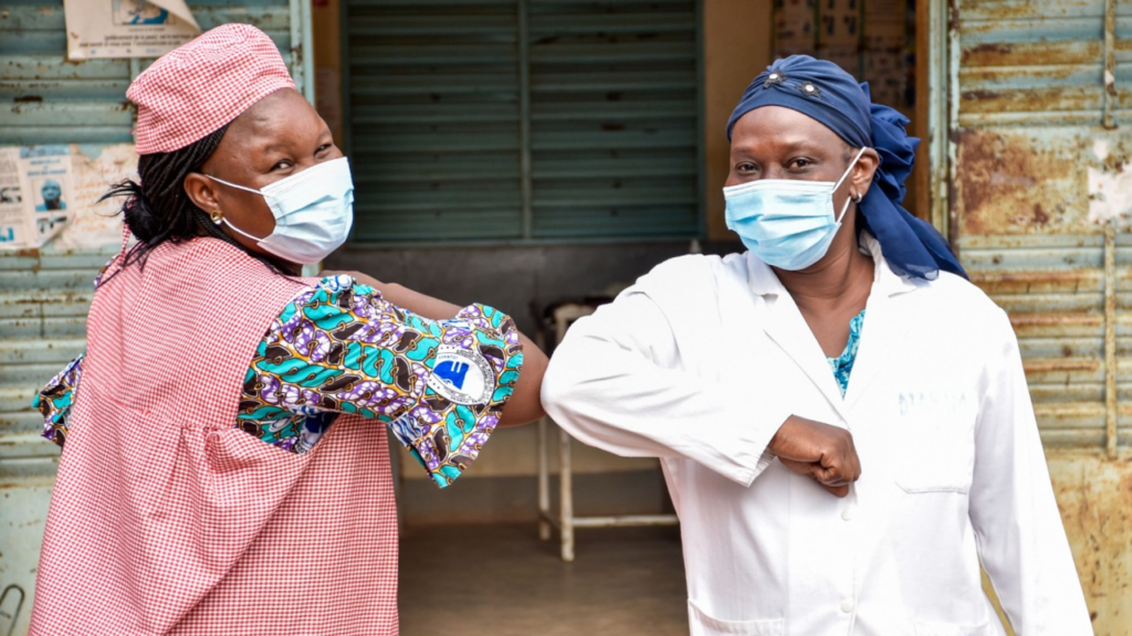 two healthcare workers in PPE bumping elbows in greeting